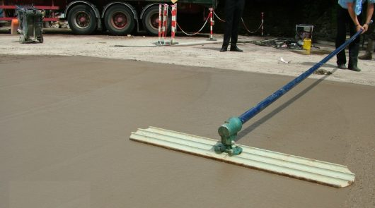 Worker using the Belle easy bull float on wet concrete to smooth it out on a work site