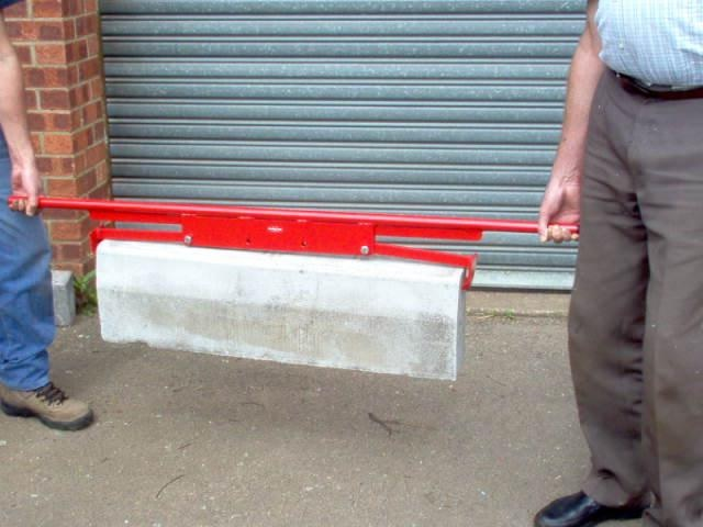 Two people using the red steel end gripping kerb/slab lifter from Mustang to lift a concrete slab