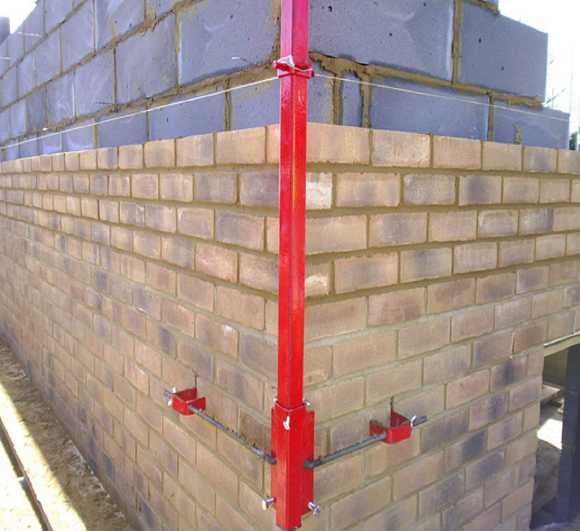 Red steel Mustang 6' External Profile fixed onto the outside corner of a wall in the process of being built
