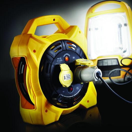 Black and yellow Defender 20M box cable reel with Defender fluorescent floor light plugged into one of the power outlets