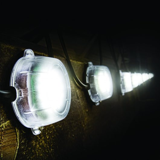 Defender 50M LED festoon hanging light chain hanging on a wall with lights turned on