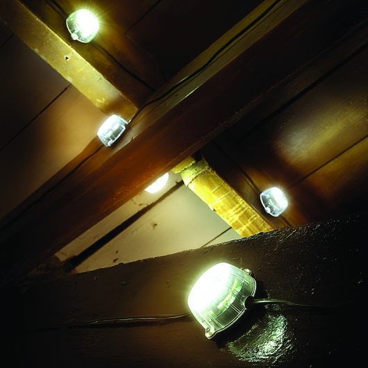 Defender 50M LED festoon hanging light chain scattered around attached to multiple wooden beams, turned on