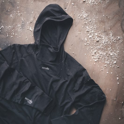 Charcoal marl polyester active hoodie with contrasting grey Scruffs logo on chest and sleeve laid on a wooden surface