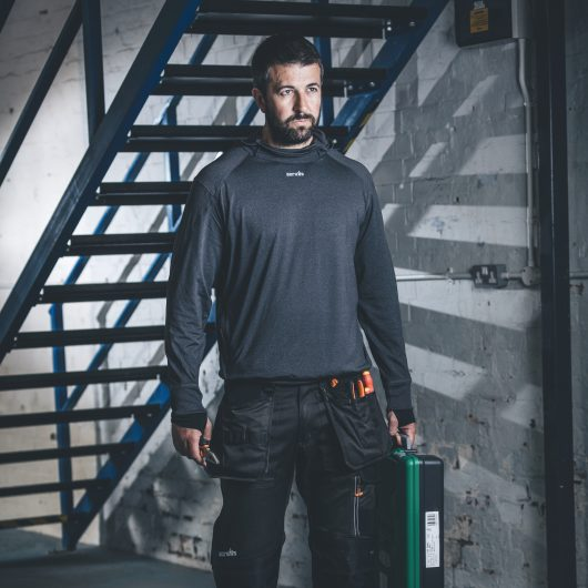 Man holding a toolbox wearing the charcoal marl Scruffs active hoodie and 3D trade trousers with stairs in the background