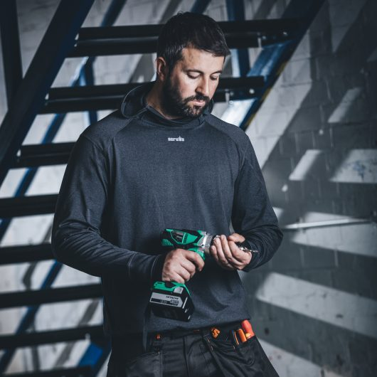 Man holding a drill wearing the charcoal marl Scruffs active hoodie and 3D trade trousers with stairs in the background
