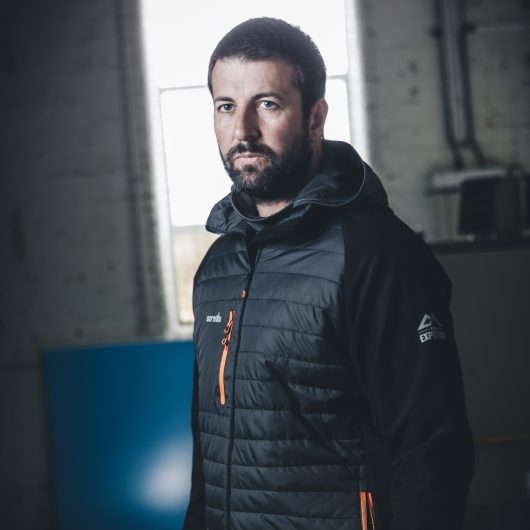 Man layering the charcoal marl Scruffs active hoodie underneath the Scruffs expedition thermo softshell jacket