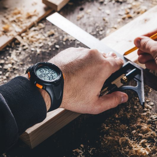 Worker wearing the Scruffs activity tracker watch whilst measuring and drawing on a plank of wood with a pencil