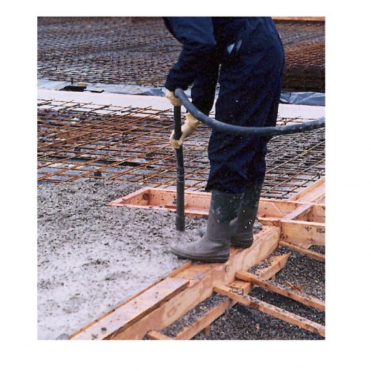 Worker wearing overalls and wellies using the Belle BGA mechanical concrete poker in wet concrete onsite