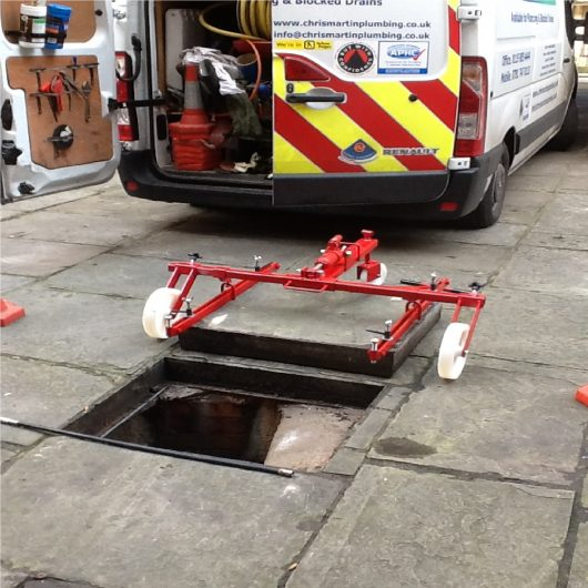 Red steel Mustang hydraulic manhole cover lifter with white wheels lifting a square manhole cover