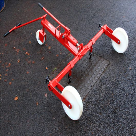 Mustang hydraulic manhole cover lifter made from red steel with white wheels, black knobs and handles over manhole cover
