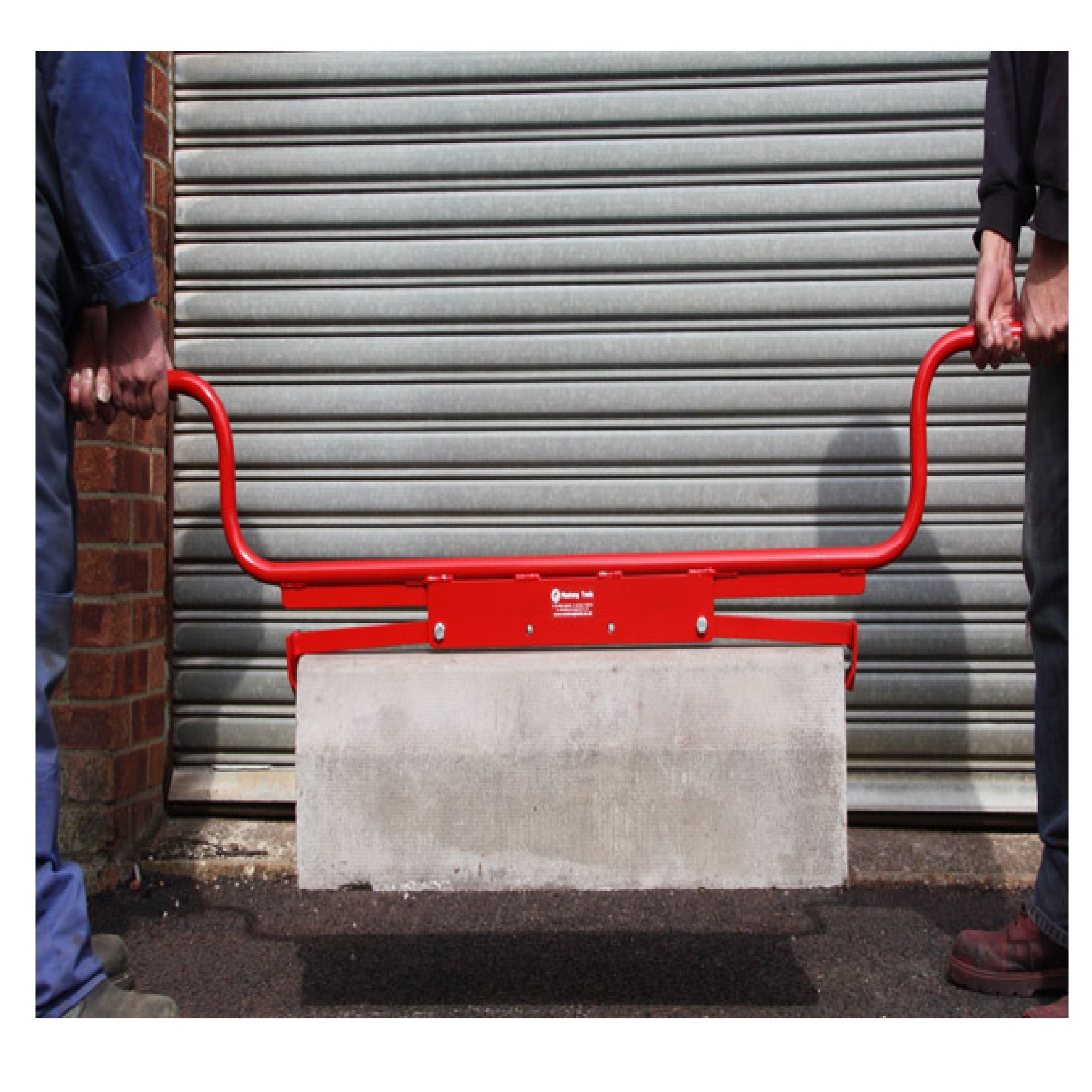2 men using the red steel Mustang high handle end gripping kerb/slab lifter to lift a slab, with garage door in background