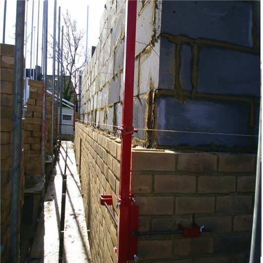 Red steel 6' Mustang external building profile attached to a wall in the process of being built