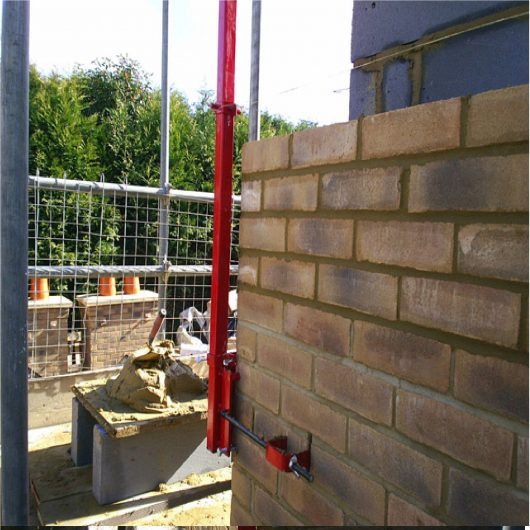 Side view of red steel 6' Mustang external building profile attached to a wall in the process of being built