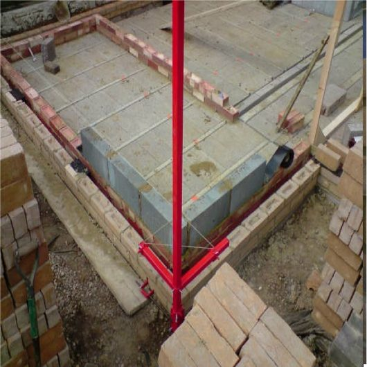 Red steel 6' external building profiles from Mustang attached to a partially built building, surrounded by piles of bricks