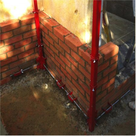 2 red steel Mustang 8' internal building profiles attached to the corners of a wall in the process of being built