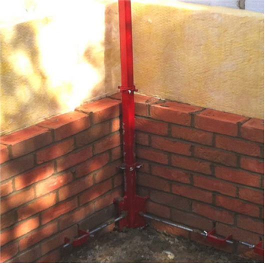 Red steel 8' Mustang internal building profile attached to the corner of a wall that is being built