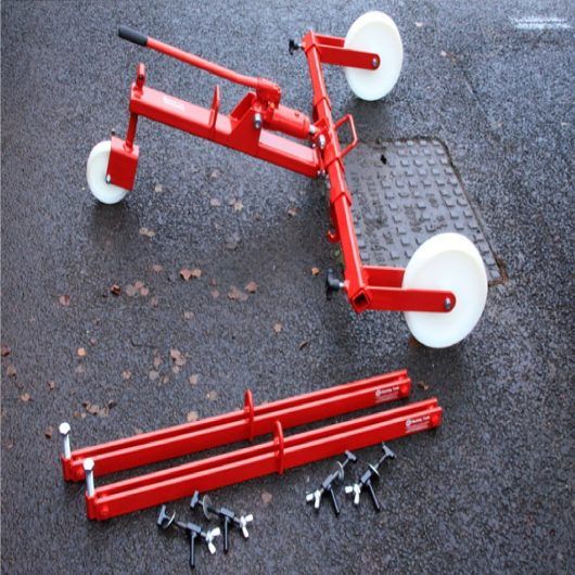 Red steel Mustang hydraulic manhole cover lifter over manhole cover next to 700mm Mustang spreader bars, on concrete