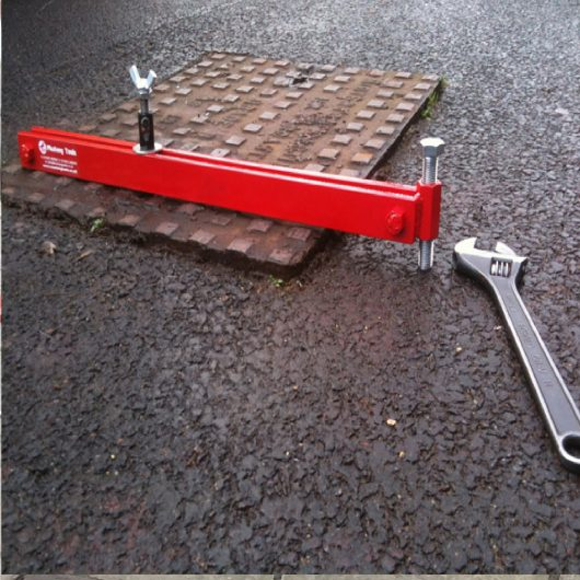 700mm long red steel Mustang manhole cover seal breaker attached to a manhole cover with spanner laying next to it