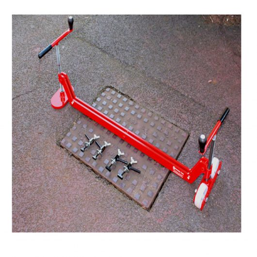 Red steel Mustang chinook manhole cover lifter with interchangeable keys on top of a manhole cover
