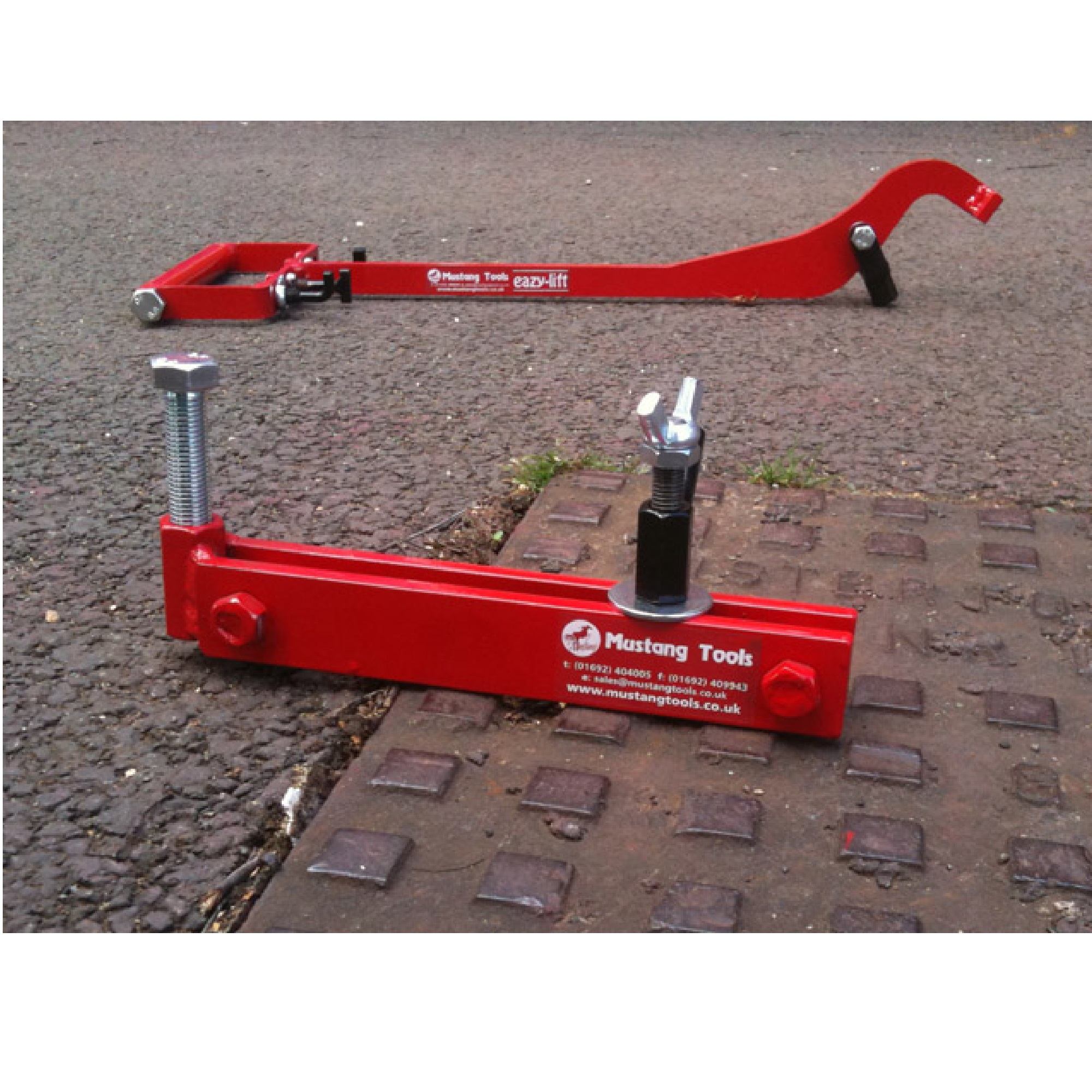 Red steel Mustang mini seal breaker on a manhole cover with the Mustang eazy lift in the background