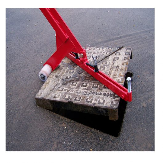Red steel Mustang pivot lift manhole cover lifter with white wheels lifting a square manhole cover