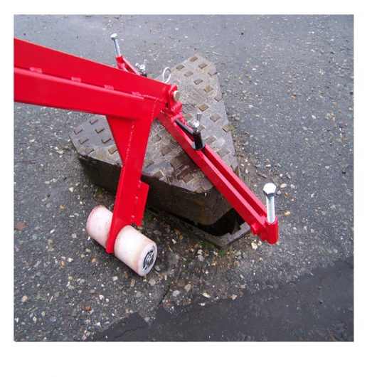 Red steel Mustang pivot lift manhole cover lifter with white wheels lifting a triangular manhole cover