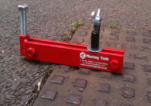 Red steel Mustang mini seal breaker on a manhole cover