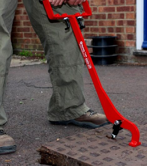 Man using the red steel eazy lift manhole cover lifter to lift a metal manhole cover