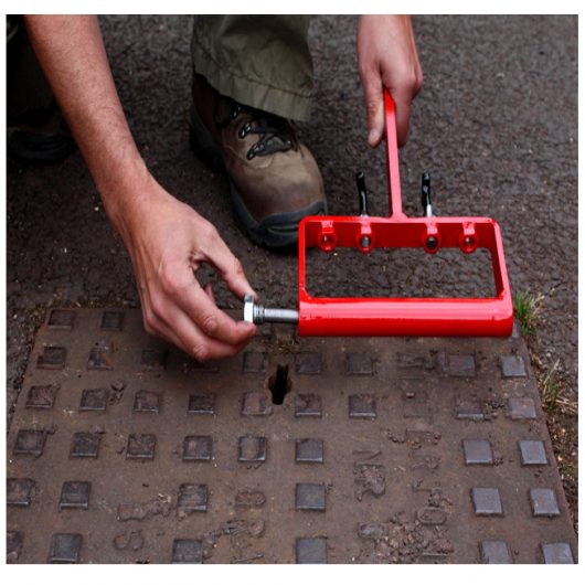 Man unscrewing dirt pick from the handle of the Mustang eazy lift manhole cover lifter