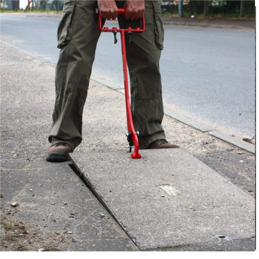 Man using the red steel eazy lift manhole cover lifter to lift a manhole cover