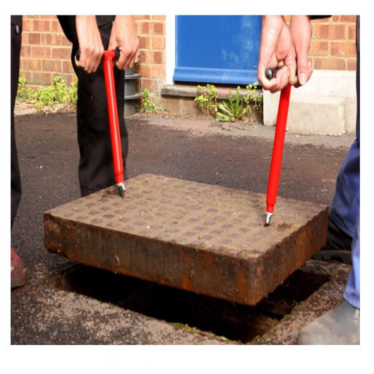2 men using the red steel Mustang mini lift manhole cover lifter to lift up a metal manhole cover
