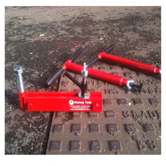 2 red steel Mustang mini lift manhole cover lifter next to a Mustang seal breaker, on top of a manhole cover