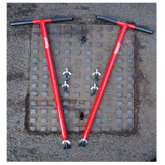 Red steel Mustang mini lift XL manhole cover lifters with interchangeable keys, laid on a manhole cover