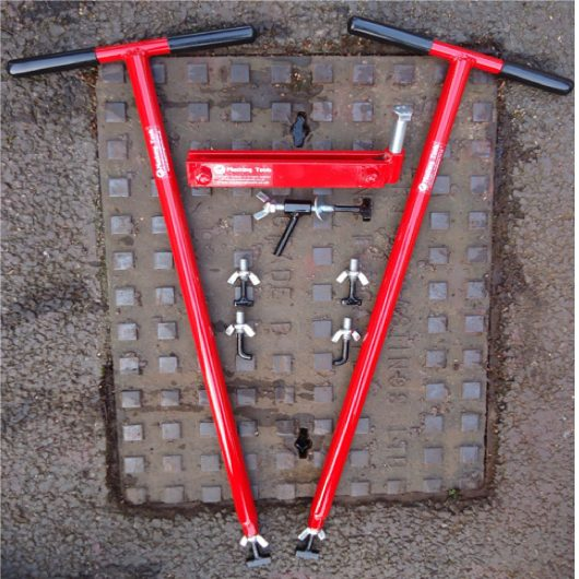 Red steel Mustang mini lift XL manhole cover lifters with interchangeable keys and seal breaker, laid on a manhole cover