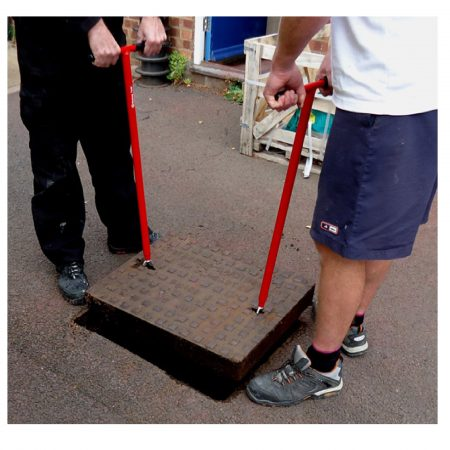2 men using the red steel Mustang mini lift XL manhole cover lifter to lift a manhole cover