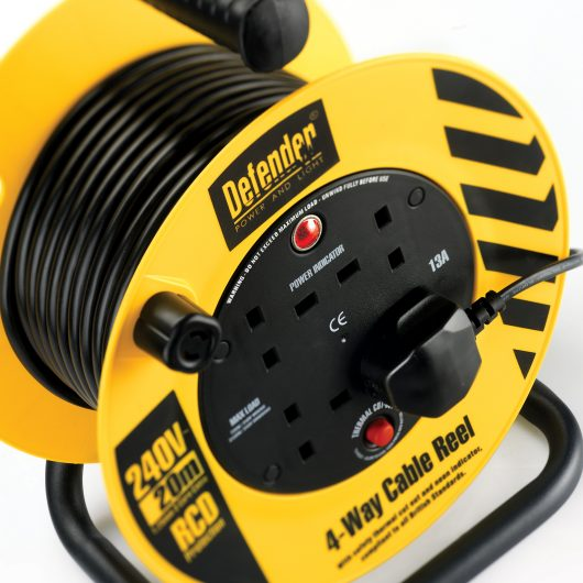 Black and yellow 20M 4-way cable reel with plug in one of the power outlets and black Defender branding on the front