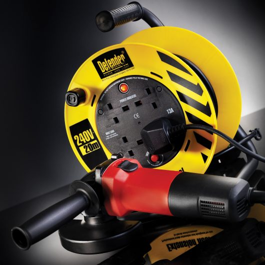 Defender 20M industrial extension reel with tool plugged into one of the power outlets and the red power indicator on