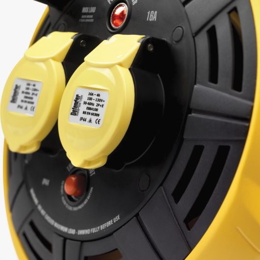 Close up of the 2 16A power outlets with yellow protective caps on the front of the Defender 15M 2-way cassette cable reel