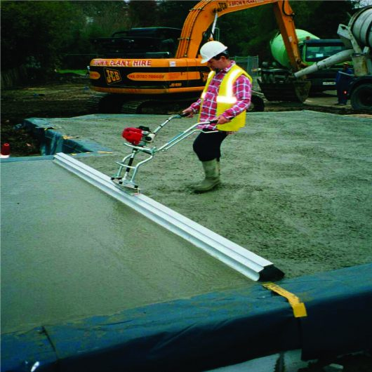 Worker wearing safety clothing using the Belle Easy Screed Pro on fresh concrete onsite with digger in background