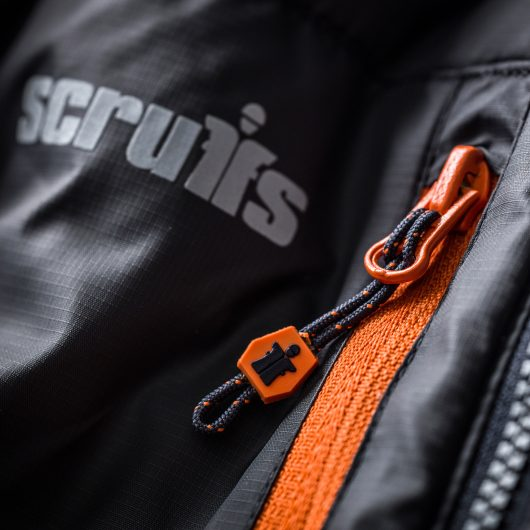 Close up of the orange chest zip and contrasting grey Scruffs logo on the expedition thermo softshell jacket