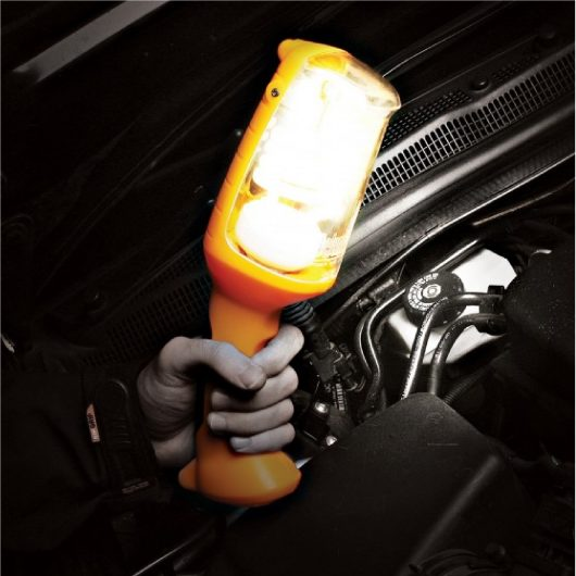 Man using the Defender fluorescent hand lamp to look under the bonnet of a vehicle