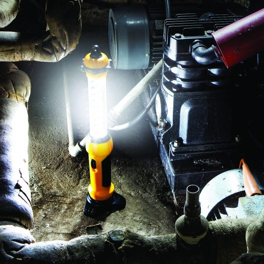 Yellow and black Defender LED hand lamp stood on floor illuminating pipes and generator