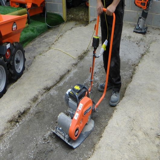 Worker wearing safety clothing using the Belle PCEL 400E electric wacker plate compactor on gravel onsite
