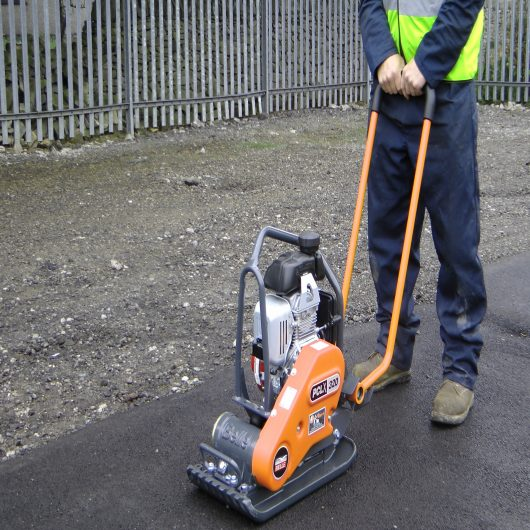 Worker wearing safety clothing using the Belle PCLX 400 wacker plate compactor on concrete