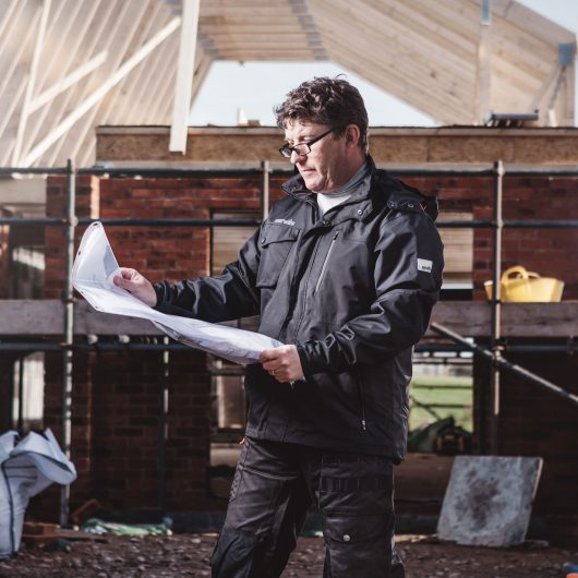 Worker looking at building plans wearing the Scruffs pro jacket, standing in-front of house in the process of being built