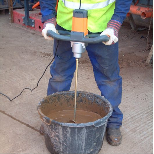 Worker wearing safety clothing using the Belle Promix 1600 hand stirrer mixer to mix in a bucket