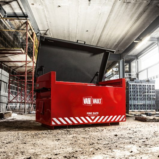 Red sheet steel Van Vault fire safe with black lid open, on a building site