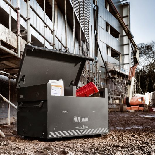 Black Van Vault fuel 'n' tool storage box with lid open and work equipment and flammable liquids in, on a building site