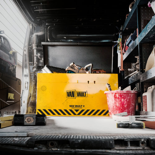 Yellow Van Vault 2 tool box made from steel in the back of a van with tools in it and building equipment around it