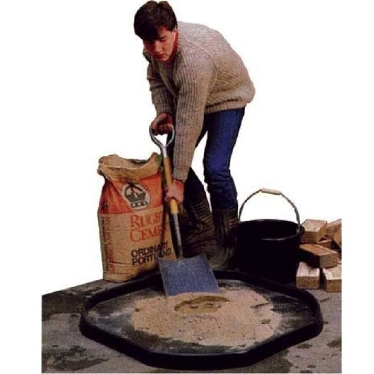 Man shovelling cement into Tufspot mixing tray with bricks and bucket next to him